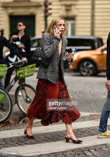 Guest is seen wearing a black and white tweed jacket and red graphic skirt with a Chanel bag outside the Altuzarra show during Paris Fashion Week...