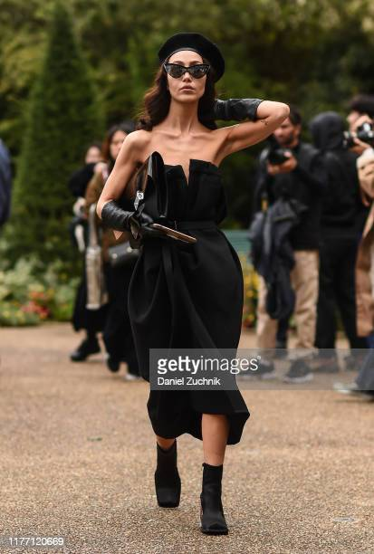 Guest is seen wearing a black beret, black Maison Margiela dress and black boots outside the Maison Margiela show during Paris Fashion Week SS20 on...