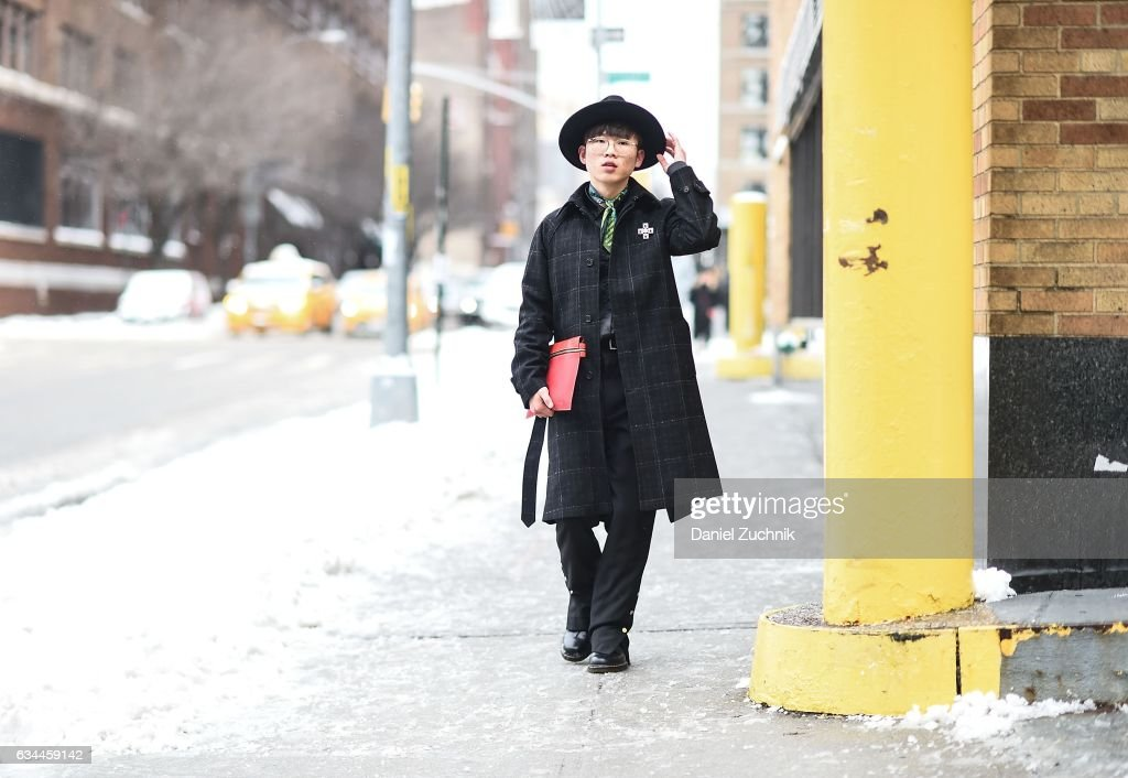 A guest is seen wearing a black checkered coat and black hat with red bag outside of the Tadashi Shoji show during New York Fashion Week: Women's Fall/Winter 2017 on February 9, 2017 in New York City.