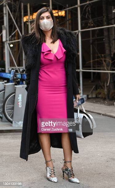 Guest is seen wearing a black coat and pink dress with snake skin heels outside the Christian Siriano show during New York Fashion Week F/W21 on...