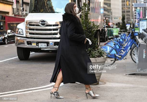 Guest is seen wearing a black coat and pink dress with snake skin outside the Christian Siriano show during New York Fashion Week F/W21 on February...