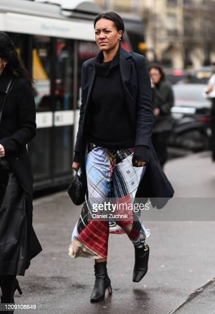 A guest is seen wearing a black coat black sweater and plaid skirt with black boots outside the Ann Demeulemeester show during Paris Fashion Week...