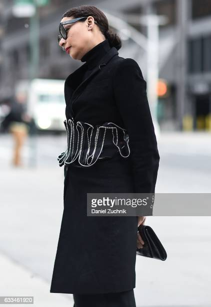 A guest is seen wearing a black coat with black and white belt outside of the Rochambeau show during New York Fashion Week Men's AW17 on February 1...