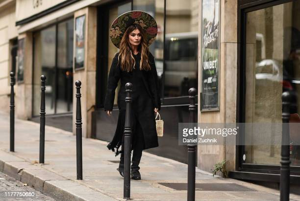 A guest is seen wearing a black dress and a floral headpiece outside the Altuzarra show during Paris Fashion Week SS20 on September 28 2019 in Paris...