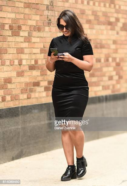 A guest is seen wearing a black dress outside the General Idea show during New York Fashion Week Men's S/S 2018 at Skylight Clarkson Sq on July 13...