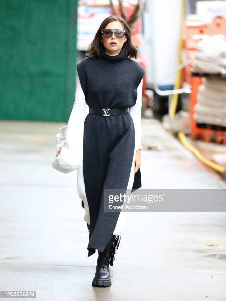 Guest is seen wearing a black dress with white long sleeved shirt, Louis Vuitton belt, a white Maison Margiela handbag and sunglasses outside of the...