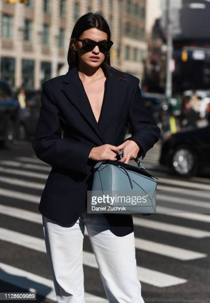 A guest is seen wearing a black jacket blue bag and white pants outside the Self Portrait show during New York Fashion Week Fall/Winter 2019 on...