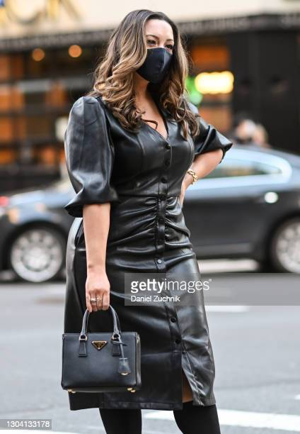 Guest is seen wearing a black leather dress and Prada bag outside the Christian Siriano show during New York Fashion Week F/W21 on February 25, 2021...