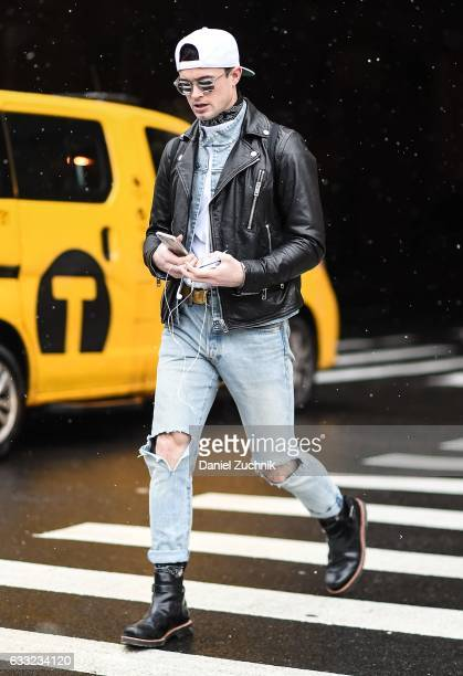 A guest is seen wearing a black leather jacket blue ripped jeans black boots and white hat outside of the Carlos Campos show during New York Fashion...