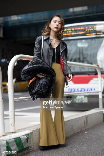 A guest is seen wearing a black leather jacket with olive pants and black top during the Amazon Fashion Week TOKYO 2018 A/W on March 23 2018 in Tokyo...