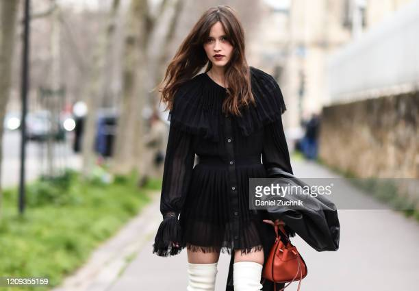 A guest is seen wearing a black Loewe top and red bag outside the Loewe show during Paris Fashion Week AW20 on February 28 2020 in Paris France
