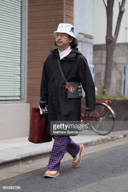 A guest is seen wearing a black raincoat with white bucket hat during the Amazon Fashion Week TOKYO 2018 A/W on March 19 2018 in Tokyo Japan