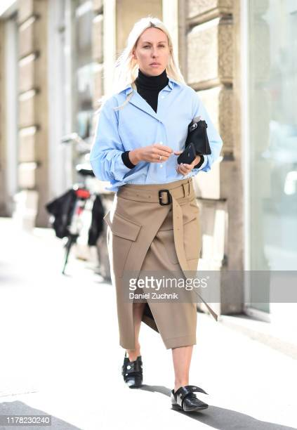 Guest is seen wearing a blue blouse, beige skirt outside the APC show during Paris Fashion Week SS20 on September 30, 2019 in Paris, France.