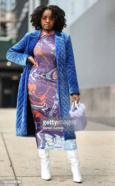 Guest is seen wearing a blue coat, purple print dress and white boots with a purple bag outside the Rebecca Minkoff show during New York Fashion Week...