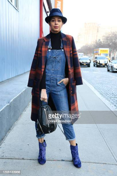 Guest is seen wearing a blue hat, jacket, blue overalls, black handbag and blue heels at the Rebecca Minkoff show during New York Fashion Week on...