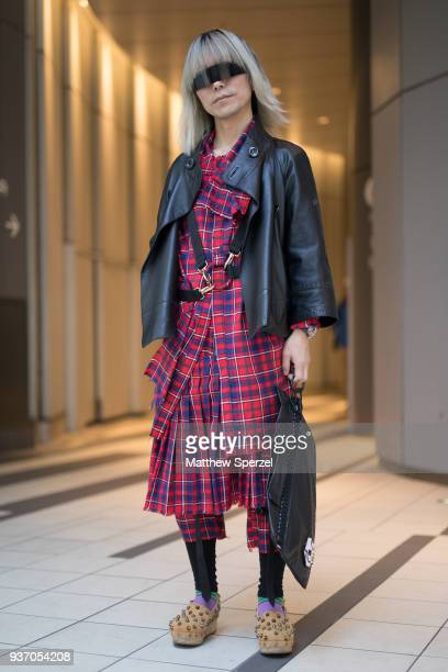 Guest is seen wearing a blue/red plaid outfit with black leather jacket, harness, studded shoes, and visor sunglasses during the Amazon Fashion Week...