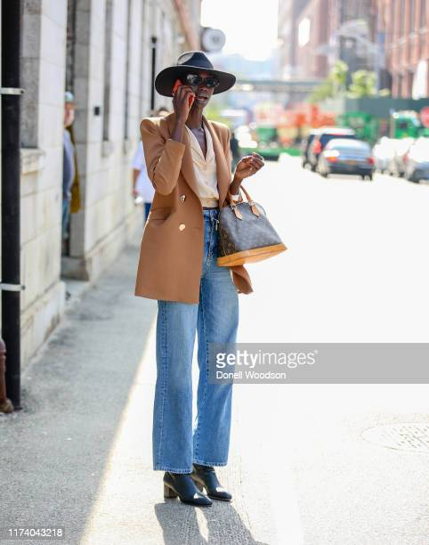 Guest is seen wearing a brown blazer, beige top and blue jeans during New York Fashion Week on September 11, 2019 in New York City.