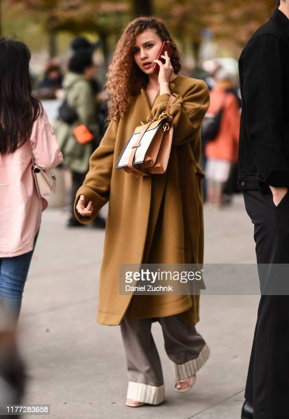 A guest is seen wearing a brown Chloe coat and bag outside the Chloe show during Paris Fashion Week SS20 on September 26 2019 in Paris France