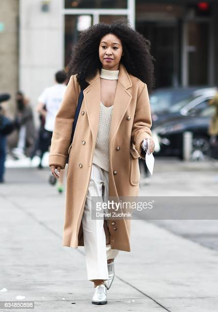 A guest is seen wearing a brown coat and beige top and pants at the Dion Lee show during New York Fashion Week Women's Fall/Winter 2017 on February...