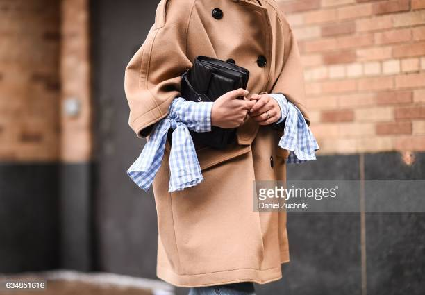 A guest is seen wearing a brown coat and blue jeans at the Dion Lee show during New York Fashion Week Women's Fall/Winter 2017 on February 11 2017 in...