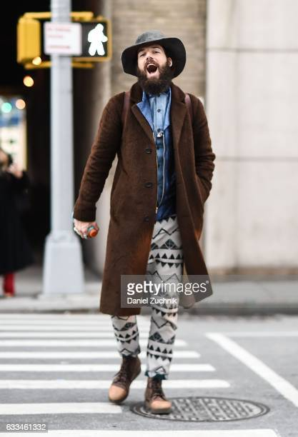 A guest is seen wearing a brown coat blue jean shirt native pants and gray hat outside of the Rochambeau show during New York Fashion Week Men's AW17...