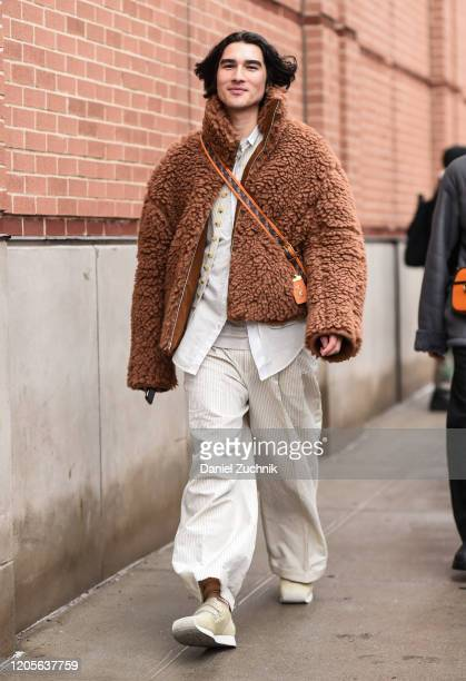 Guest is seen wearing a brown coat, white top, white pants and Coach bag outside the Coach 1941 show during New York Fashion Week: A/W20 on February...