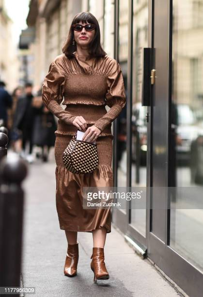 A guest is seen wearing a brown dress and shoes with a checkered bag outside the Thom Browne show during Paris Fashion Week SS20 on September 29 2019...