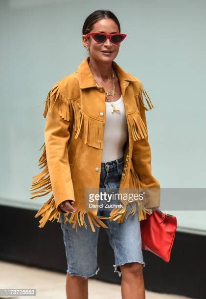 A guest is seen wearing a brown leather fringe jacket white top blue jean shorts and red sunglasses outside the Vera Wang show during New York...