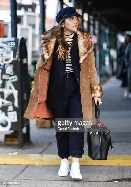 A guest is seen wearing a brown leather fur trimmed coat outside the Tadashi Shoji show during New York Fashion Week Women's A/W 2018 on February 8...