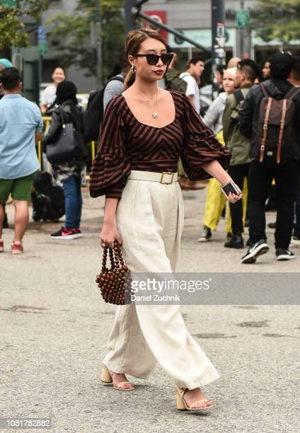 A guest is seen wearing a brown striped top and beige pants outside the Coach 1941 show during New York Fashion Week Women's S/S 2019 on September 11...