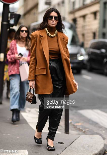 A guest is seen wearing a brown Thom Browne jacket and black leather pants with a gold chain and animal print purse outside the Thom Browne show...