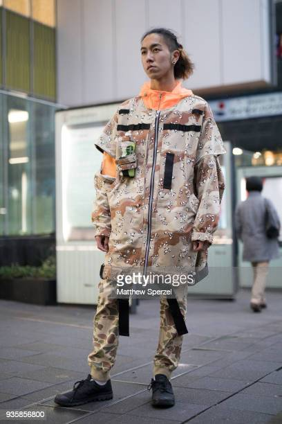 A guest is seen wearing a camo outfit with neon orange jacket during the Amazon Fashion Week TOKYO 2018 A/W on March 21 2018 in Tokyo Japan