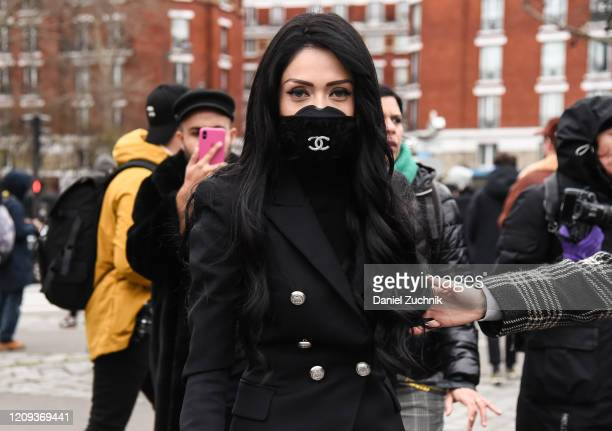 A guest is seen wearing a Chanel mask outside the Balmain show during Paris Fashion Week AW20 on February 28 2020 in Paris France
