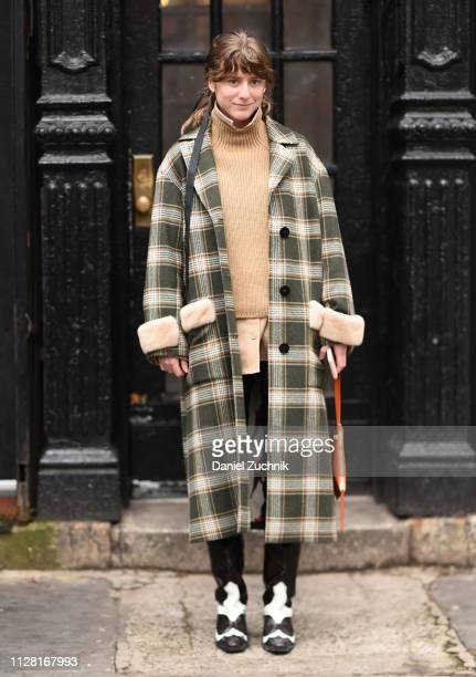 Guest is seen wearing a checkered coat, beige sweater and black and white shoes outside the Maryam Nassir Zadeh show during New York Fashion Week:...