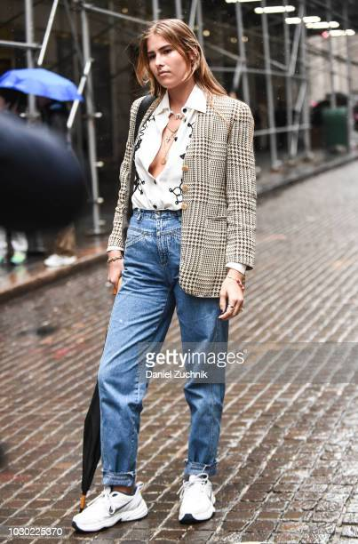 A guest is seen wearing a checkered coat white top and blue jeans with Nike sneakers outside the Tibi show during New York Fashion Week Women's S/S...