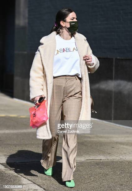 Guest is seen wearing a cream coat, Casablanca shirt, plaid pants, green shoes and pink bag outside the Rebecca Minkoff show during New York Fashion...