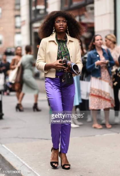 A guest is seen wearing a cream coat floral top and purple pants outside the Cynthia Rowley show during New York Fashion Week S/S20 on September 10...