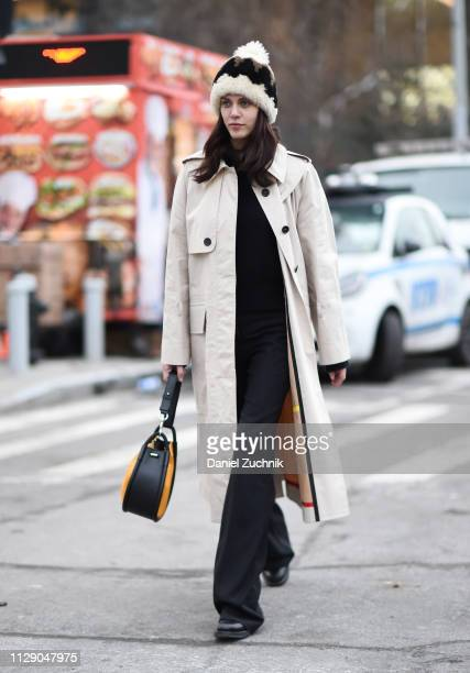 A guest is seen wearing a cream coat Proenza Schouler bag and fur beanie outside the Proenza Schouler show during New York Fashion Week Fall/Winter...