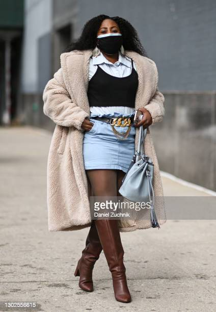 Guest is seen wearing a cream coat, white top, jean skirt and brown boots outside the Rebecca Minkoff show during New York Fashion Week F/W21 at...