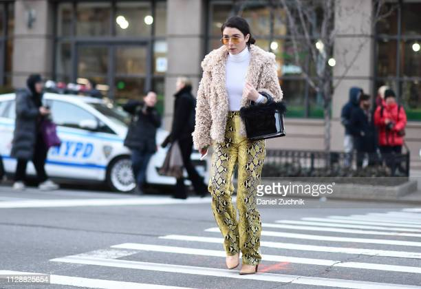 A guest is seen wearing a cream fur coat white top and snake skin pants outside the Sies Marjan show during New York Fashion Week Fall/Winter 2019 on...