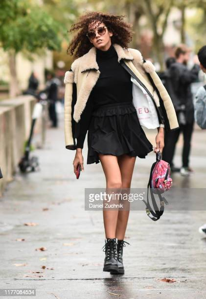 Guest is seen wearing a cream fur jacket and black dress outside the Mugler show during Paris Fashion Week SS20 on September 25, 2019 in Paris,...