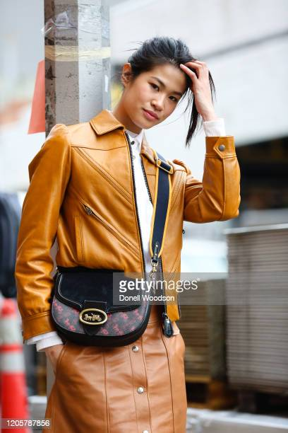 Guest is seen wearing a dark yellow coat, white shirt, brown skirt and black purse outside of the Coach 1941 show during New York Fashion Week on...