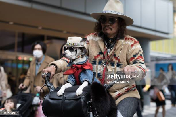 A guest is seen wearing a denim jacket red scarf and feather hat during the Amazon Fashion Week TOKYO 2018 A/W on March 24 2018 in Tokyo Japan