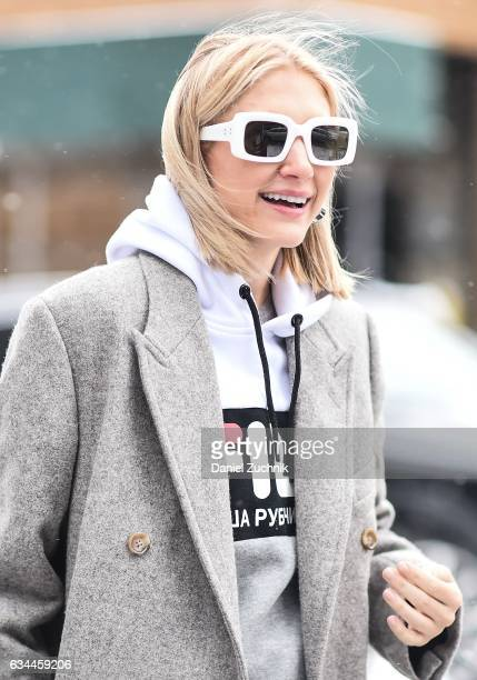 A guest is seen wearing a Fila hoodie gray coat and white sunglasses during New York Fashion Week Women's Fall/Winter 2017 on February 9 2017 in New...