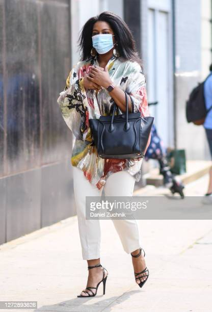 A guest is seen wearing a floral blouse white pants with black bag outside the Studio 189 show during New York Fashion Week S/S21 on September 16...