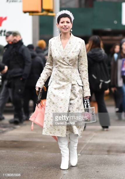 Guest is seen wearing a floral coat, white boots, with a headpiece and pearl earrings outside the Hellessy show during New York Fashion Week:...