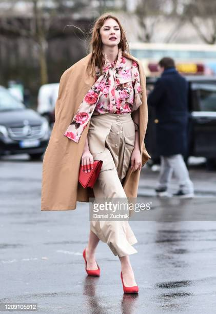 Guest is seen wearing a floral top, beige skirt, beige shaw and red triangular purse outside the Ann Demeulemeester show during Paris Fashion Week:...