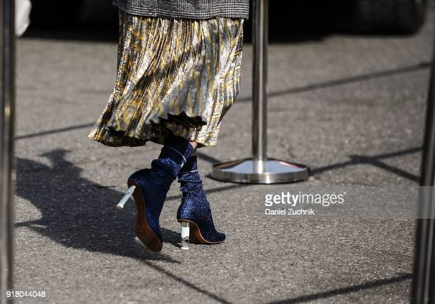A guest is seen wearing a gold and silver skirt and blue sparkly shoes outside the Coach show during New York Fashion Week Women's A/W 2018 on...