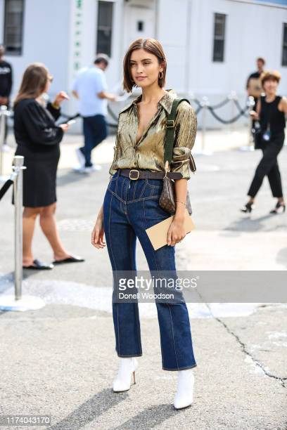 Guest is seen wearing a gold tops and blue jeans during New York Fashion Week on September 11, 2019 in New York City.