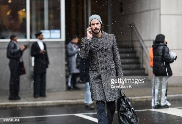 A guest is seen wearing a gray coat outside of the Carlos Campos show during New York Fashion Week Men's AW17 on January 31 2017 in New York City
